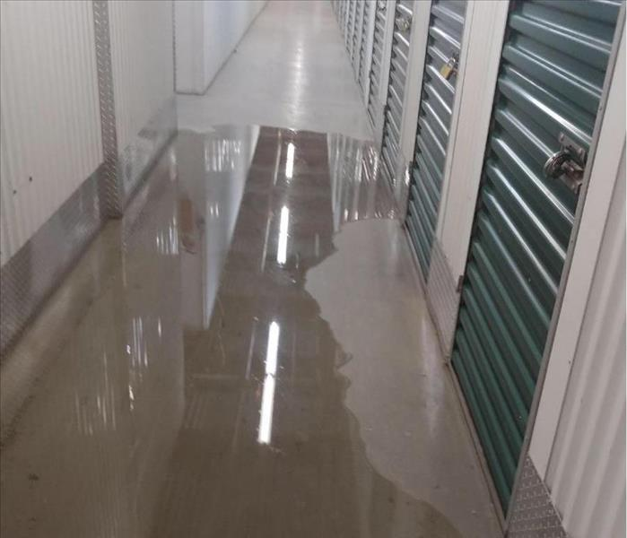 Storage unit hallway with puddle of water on the floor