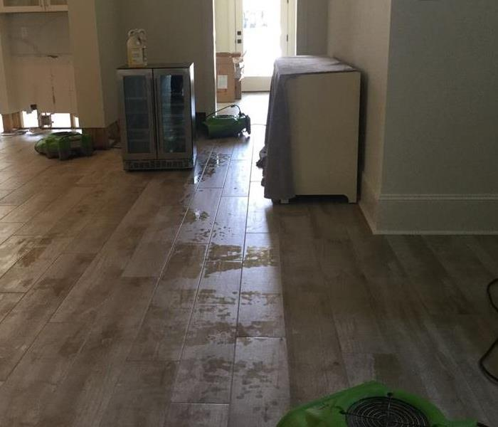 Room with wooden floors that has water on them