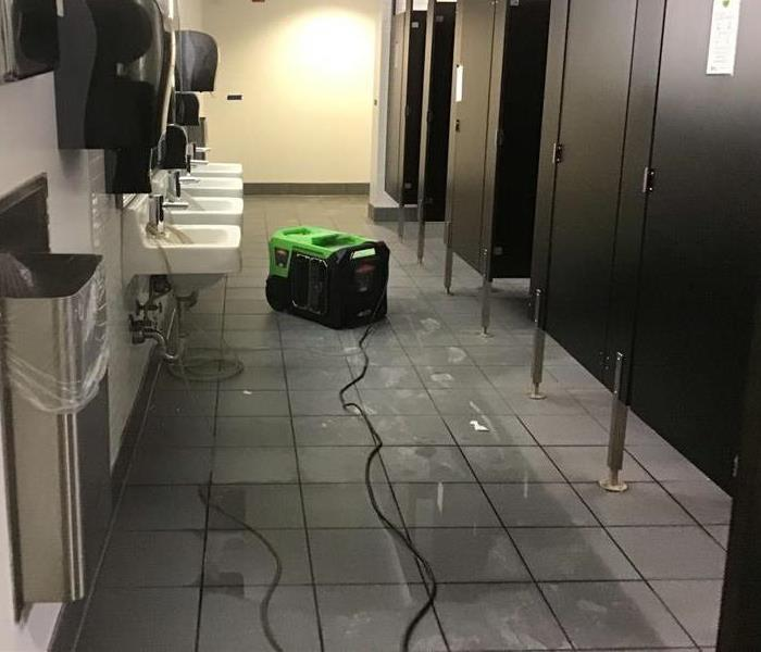 public restroom with water on floor and SERVPRO dehumidifier