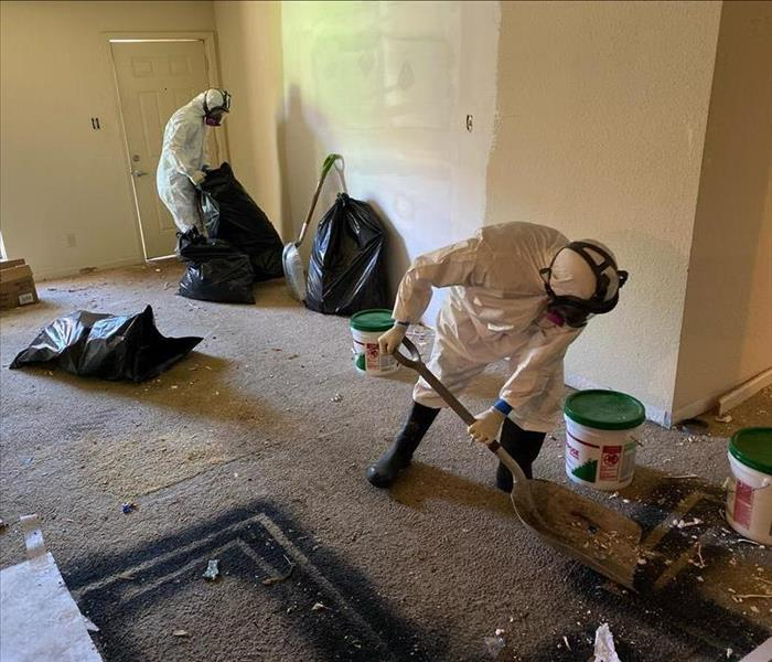 two male SERVPRO employees cleaning up fire debris