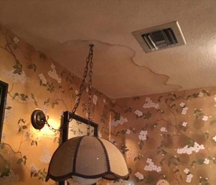 dining room with floral wallpaper and water damage stain above hanging light