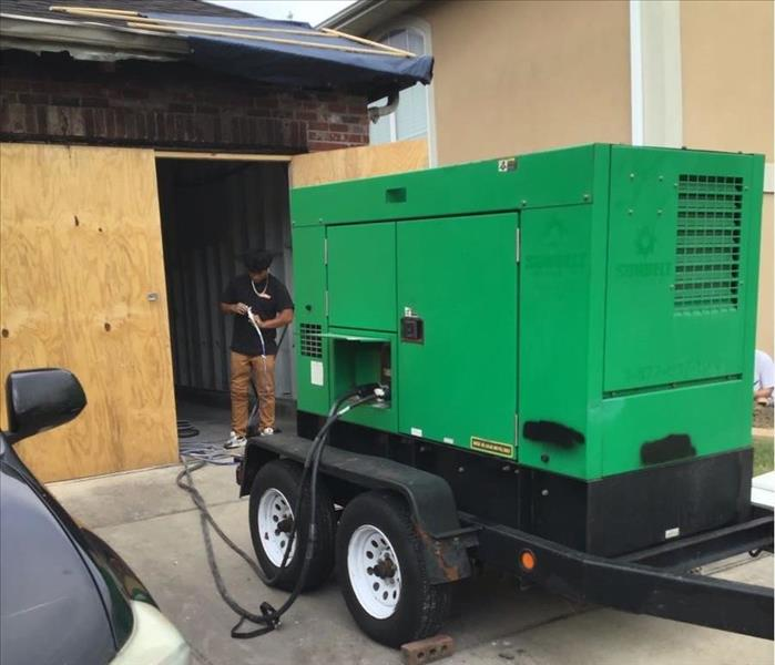 SERVPRO employee standing between garage boarded up and green generator